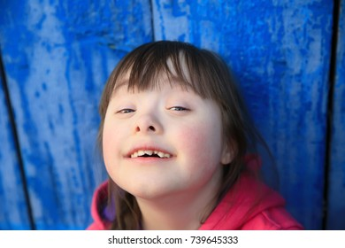 Down syndrome girl smiling on background of the blue wall.