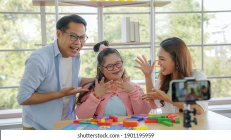 Down syndrome happy family,   Parents playing with a wooden block at home while showing their friends over the phone.