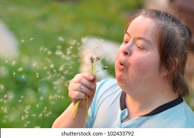 down syndrome woman blowing dandelion