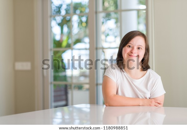 Down syndrome woman at home with a happy and cool smile on face. Lucky person.