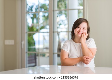 Down syndrome woman at home looking stressed and nervous with hands on mouth biting nails. Anxiety problem.