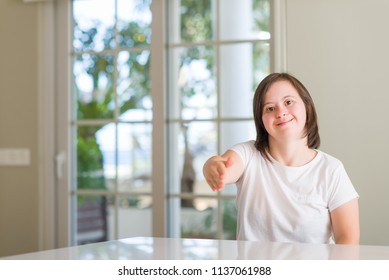 Down syndrome woman at home smiling friendly offering handshake as greeting and welcoming. Successful business.