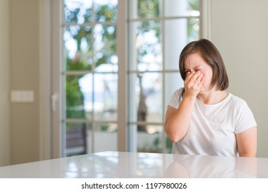 Down syndrome woman at home tired rubbing nose and eyes feeling fatigue and headache. Stress and frustration concept.
