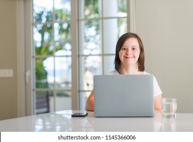 Down syndrome woman at home using computer laptop with a happy face standing and smiling with a confident smile showing teeth