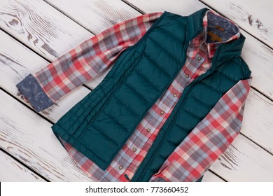 Down vest and flannel shirt with plaid pattern. Perfect for walk in cool autumn weather. Casual fashion items.
