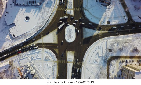 Down view of intersection in winter, circle crossroad with traffic and snow