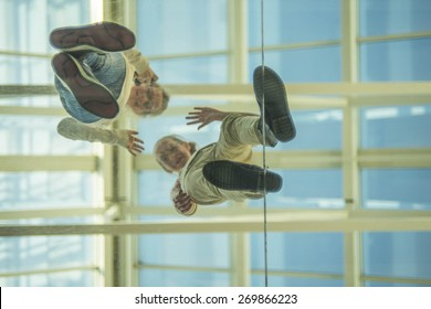 Down view Two teen girl on glass transparent blue floor waving his hand in greeting against roof and blue sky Empty space for inscription Couple of teenager up stand on plastic with smiley face
