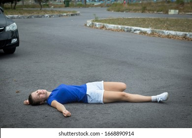 Downed girl by car, young unconscious woman lying on road, asphault, suffering from pain, injury or trauma. Inattentive person, female was hit by careless driver. Accident on road. Dangerous situation