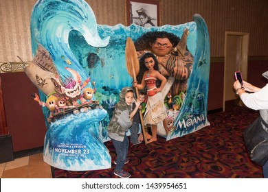 DOWNERS GROVE, ILLINOIS - NOVEMBER 12, 2016: Children being photographed by mother in movie theater life-size advertising for Disney's Moana.