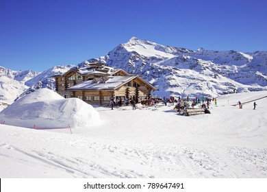 Downhill slope and apres ski mountain hut with restaurant terrace in the Italian Alps, Europe, Italy. Ski area Santa Caterina Valfurva