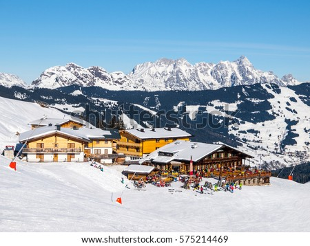 Downhill slope and apres ski mountain hut with restaurant terrace in Saalbach Hinterglemm Leogang winter resort, Tirol, Austria, Europe. Sunny day shot.