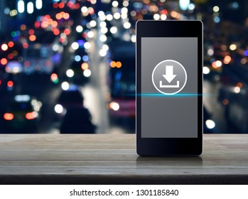 Download flat icon on modern smart mobile phone screen on wooden table over blur colorful night light city with cars in city, Business internet concept