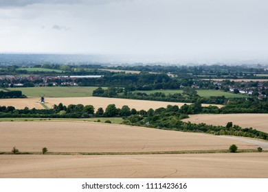 A downpour of rain shrouds villages in the agricultural landscape of Aylesbury Vale in Buckinghamshire, England, with Ivinghoe Windmill standing in fields of wheat in the foreground.
