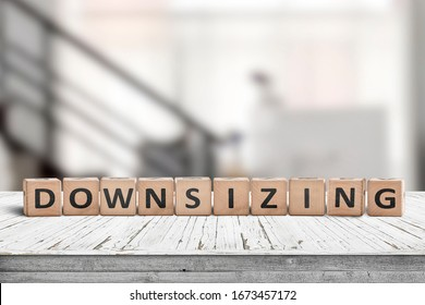 Downsizing message sign made of wood on a white desk in an office environment