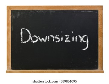 Downsizing written in white chalk on a black chalkboard isolated on white
