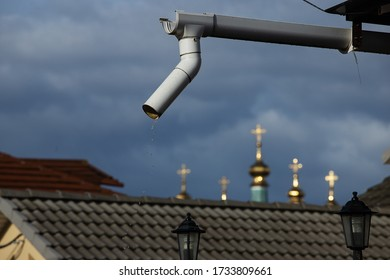 downspout on the roof of a private house, poorly organized drainage of rainwater from a height of pouring drops, against the background of storm clouds and the domes of the Church