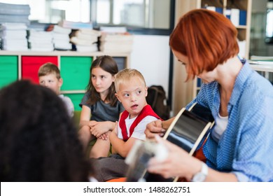 A down-syndrome boy with school kids and teacher sitting in class, playing guitar.