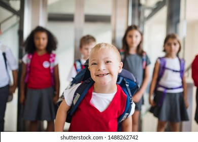 A down-syndrome school boy with group of children in corridor, walking.