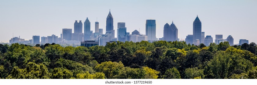 Downtown Atlanta Skyline showing several prominent buildings and hotels under a blue sky as seen from Buckhead in North Atlanta