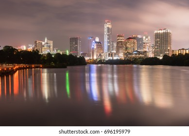 Downtown Austin, Texas, USA skylines reflection on the Colorado River at twilight. Ann and Roy Butler Hike-and-Bike Trail and boardwalk at Lady Bird Lake is on the left.