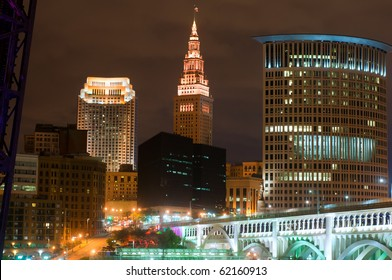 Downtown buildings of Cleveland, Ohio, lit up at night under a glowering sky