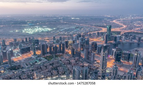 Downtown and Business bay in Dubai night to day transition timelapse. Cloudy sky and traffic on highway. Aerial view with towers and skyscrapers from Burj Khalifa viewpoint.