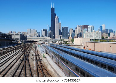 Downtown Chicago skyline over railroads with passenger trains