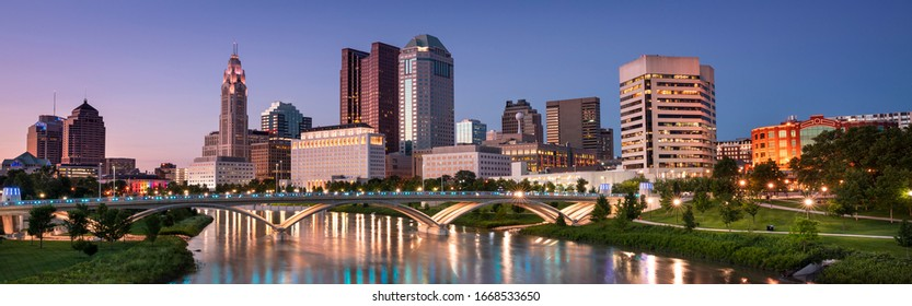 Downtown cityscape panorama looking over the Scioto River and the Discovery Bridge along the Riverfront Park in the city of Columbus Ohio USA