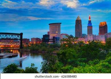 Downtown Cleveland beginning to light up at dusk with the Cuyahoga River winding past
