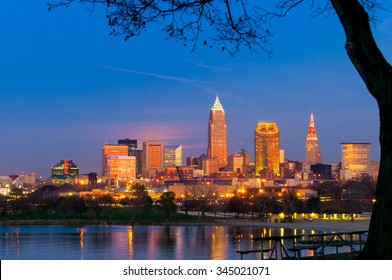Downtown Cleveland, Ohio, glows in setting sunlight as the full moon prepares to rise under the pink clouds at center left