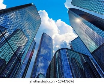 Downtown corporate business district architecture concept: glass reflective office buildings skyscrapers against blue sky with clouds and sun light