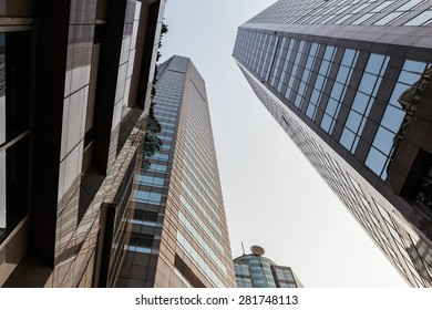 Downtown corporate business district architecture: glass reflective office buildings against blue sky