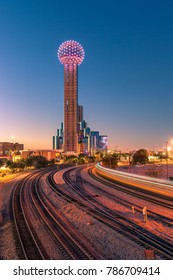 Downtown Dallas at sunset with Reunion Tower and light trail from moving train