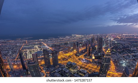 Downtown and and financial district in Dubai night to day transition timelapse. Cloudy sky and traffic on highway. Aerial view with towers and skyscrapers from Burj Khalifa viewpoint.