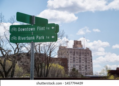 Downtown Flint and Riverbank Park bicycle path direction signs along the Flint River in Flint, Michigan.