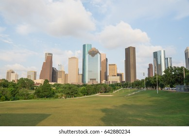 Downtown Houston at sunset with people exercising in distant. Green park lawn and modern skylines. The most populous city in Texas, and fourth-most in United States. Architecture and travel background