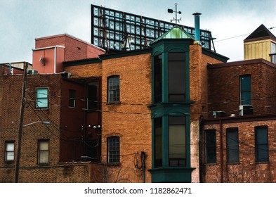 Downtown Kalamazoo buildings. Brick businesses with weather vane and back of billboard in the distance.