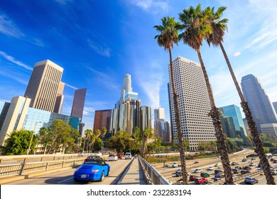 Downtown Los Angeles skyline during rush hour with blue sky