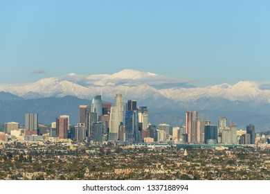 Downtown Los Angeles skyline with snow capped mountains behind at sunny day