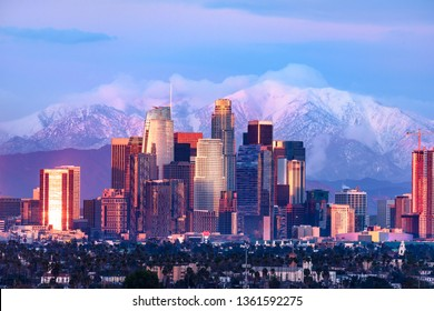 Downtown Los Angeles skyline with snow capped mountains behind at sunset
