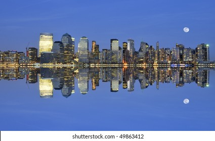 Downtown Manhattan skyline with full moon reflecting in the hudson river photographed after sunset during the magical hour