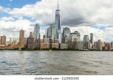 Downtown Manhattan skyline as seen from the Hudson River with the Freedom Tower in the center of the frame. White, fluffy, clouds in blue sky, water in the foreground. No people.