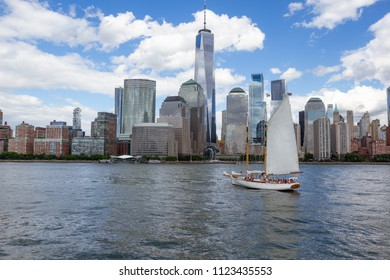 Downtown Manhattan skyline as seen from the Hudson River with the Freedom Tower in center of frame White, fluffy, clouds in blue sky, a white sailboat on water in the foreground. No people.