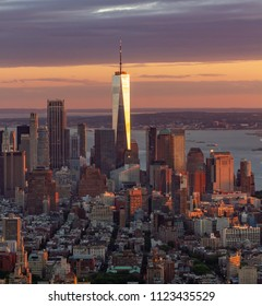 Downtown Manhattan skyline at sunset with Freedom Tower reflecting setting sun on left side of frame