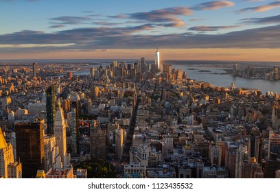 Downtown Manhattan skyline at sunset as seen from top of Empire State building. Freedom Tower is illuminated in the distance