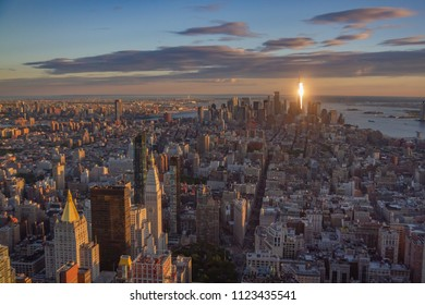 Downtown Manhattan skyline at sunset as seen from top of Empire State building. Freedom Tower is in the distance and is reflecting setting sun like a beacon of light.