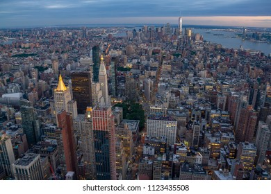 Downtown Manhattan skyline at twilight/blue hour as seen from top of Empire State building. Freedom Tower is illuminated in the distance
