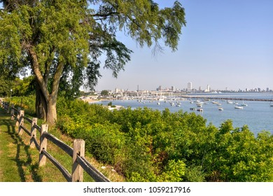 Downtown Milwaukee, Wisconsin and it's harbor in Lake Michigan is framed by greenery and a wood fence along the Oak Leaf trail.