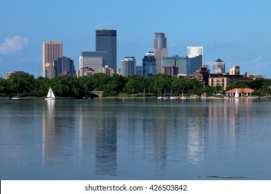 Downtown Minneapolis skyline reflecting in Lake Calhoun with sail boat.