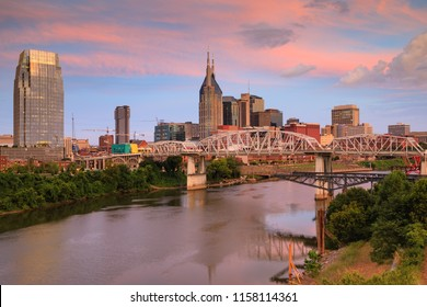 Downtown Nashville, Tennessee skyline at sunrise over the Cumberland River.